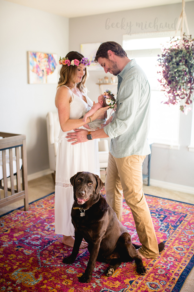 A couple and their dog pose with their new baby in their Northern Colorado home in baby's boho nursery