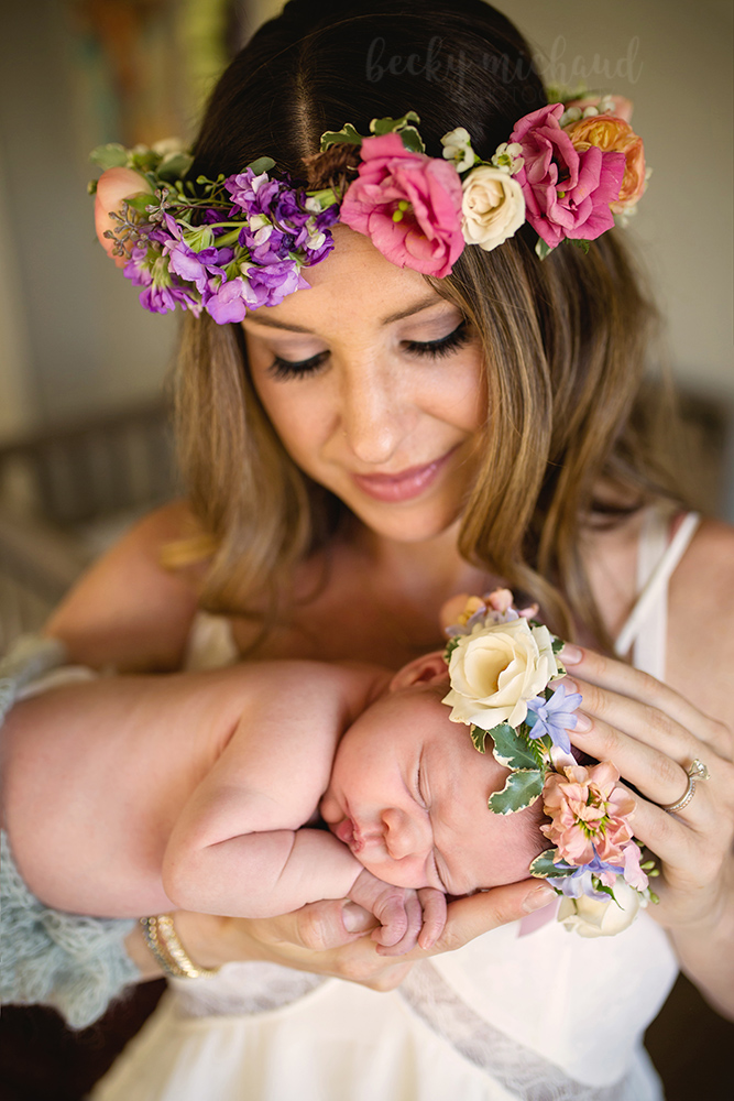 A new mom holds her baby girl while they both wear flower crowns for a newborn session