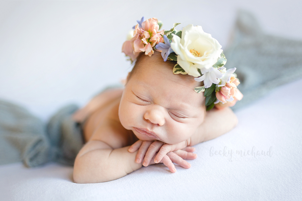 A baby girl wearing a flower crown poses on a white backdrop during her newborn photo session in her Timnath home