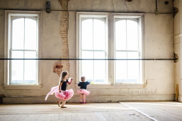 Two little dancers wearing tutus run around a big empty room in an Old Town Fort Collins building