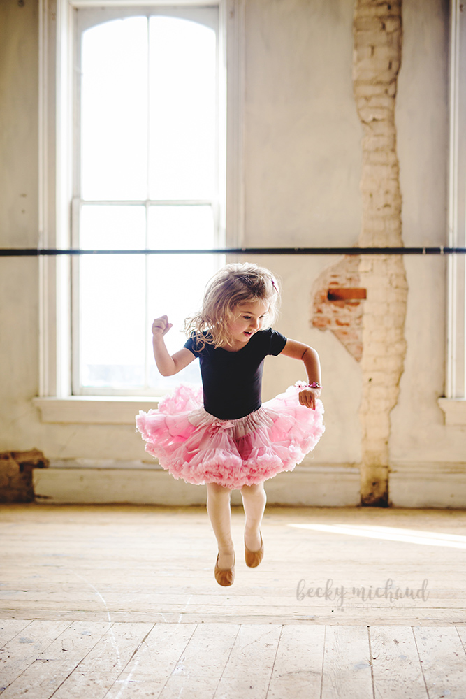 A little girl in a black leotard and pink tutu jumps and dances at the Merchant Room in Old Town Fort Collins