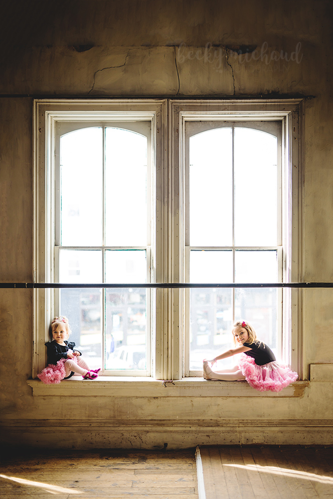 Two sisters in pink tutus sit on the window sills of a big building in Old Town Fort Collins