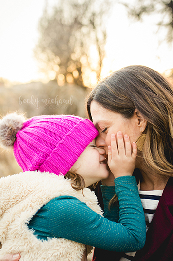 A little girl with a pink stocking cap nuzzles her mom as they explore a Fort Collins natural area during their family photo session