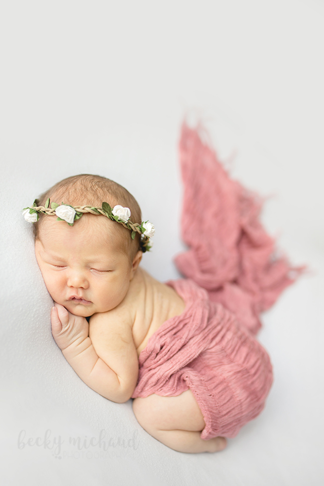 A photo of a newborn baby girl taken in her Loveland, Colorado home where she is wearing a white flower crown and a pink wrap