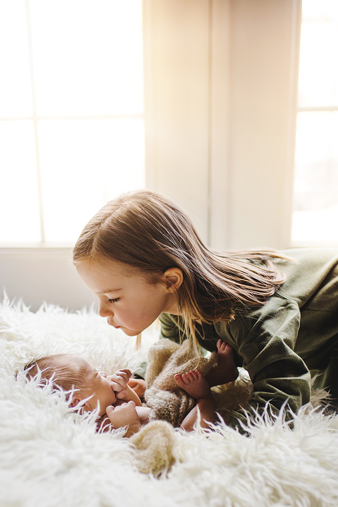 A little girl kisses her newborn baby brother in their Fort Collins home in a photo taken by Becky Michaud, Fort Collins baby photographer