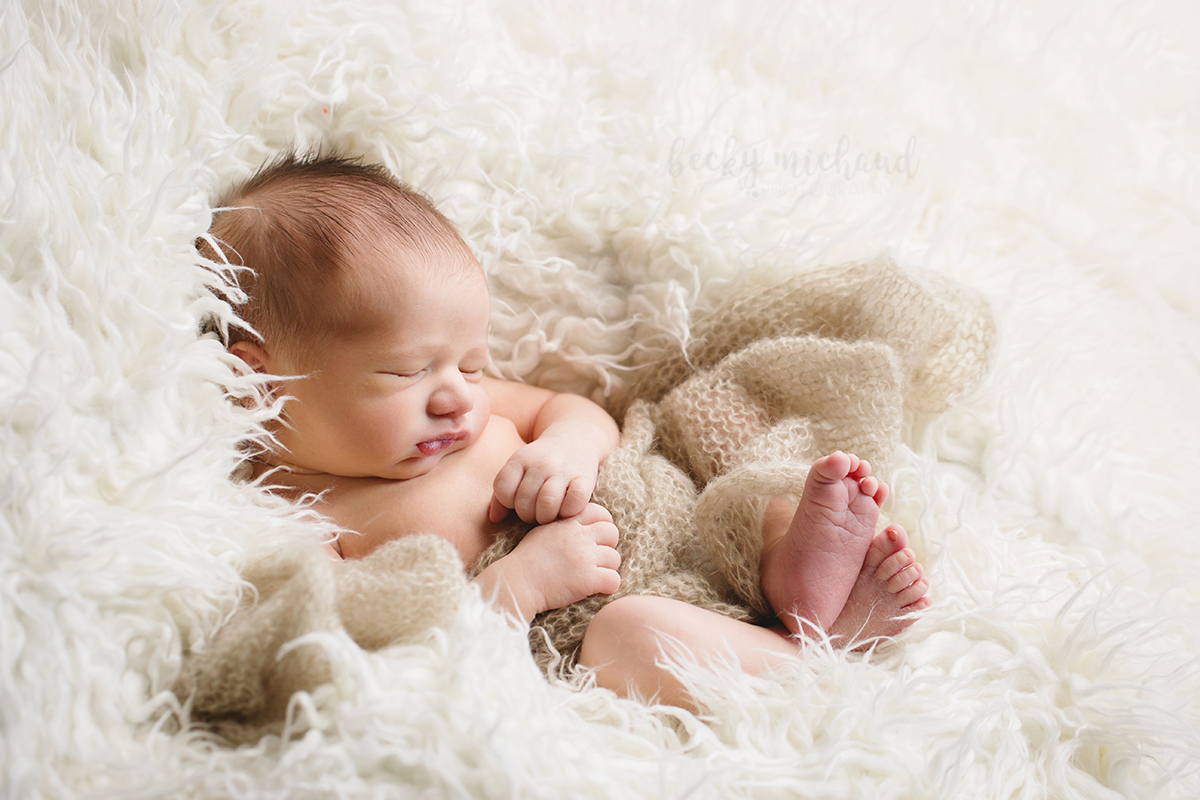 A baby boy snuggles down into a cream colored faux fur blanket during his newborn photo session in his Fort Collins home