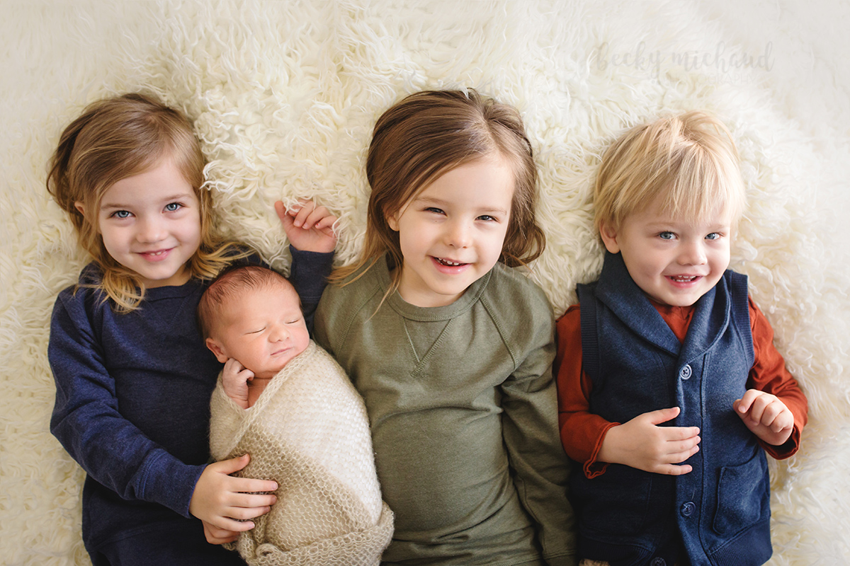 A newborn baby cuddles with his three older siblings during their photo shoot in the comfort of their home