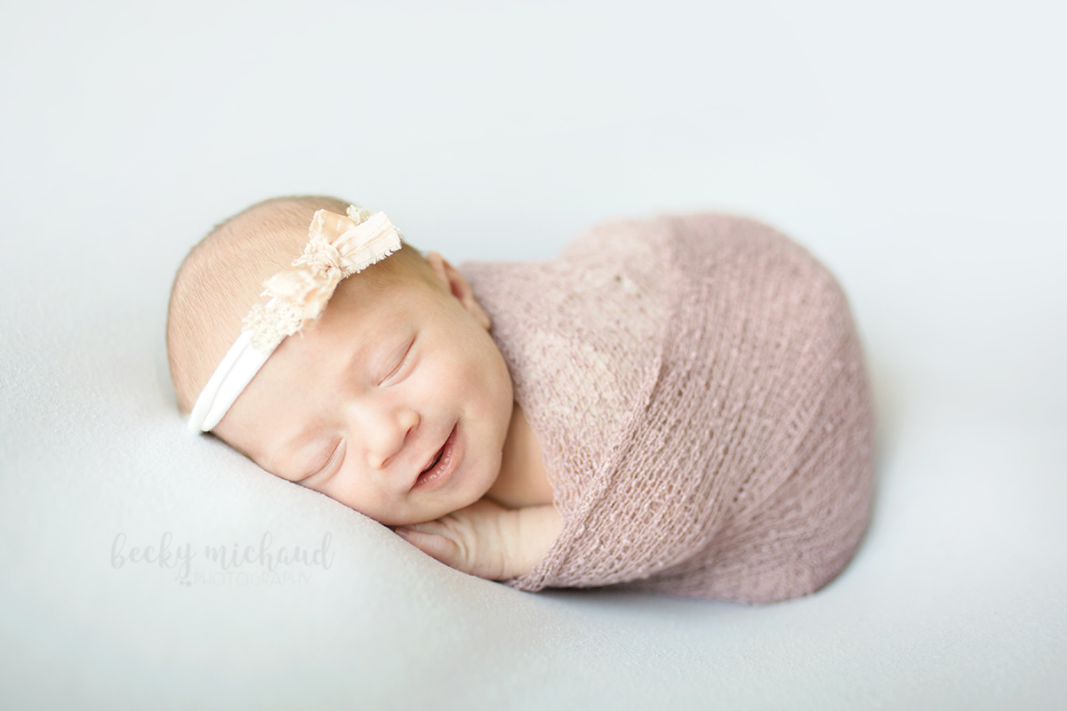 Smiling newborn baby in a mauve colored wrap wearing a headband by Edna Magdalene