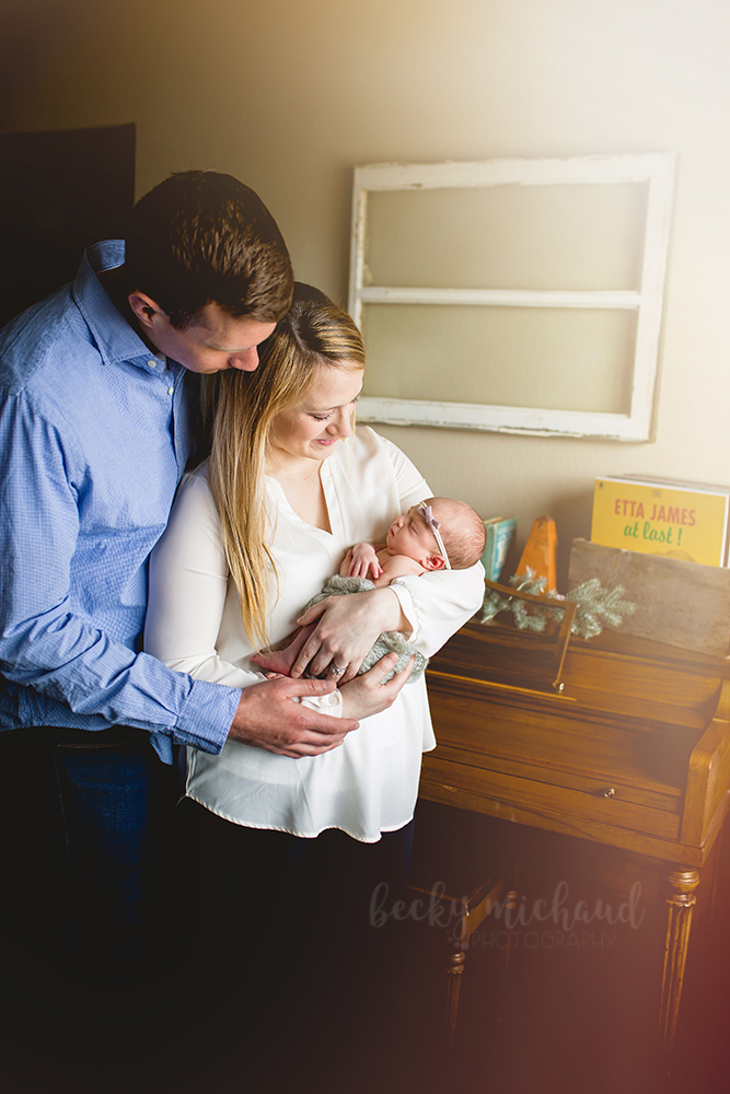 A family of three stands by their piano in a lifestyle newborn photo taken in their Loveland, Colorado home
