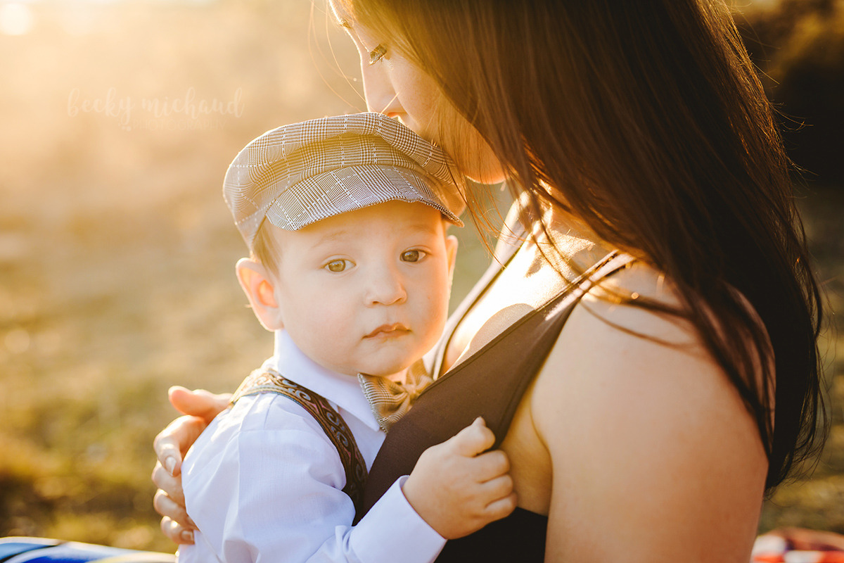 A mom kisses her little boy as he cuddles on her lap for his Northern Colorado photo shoot