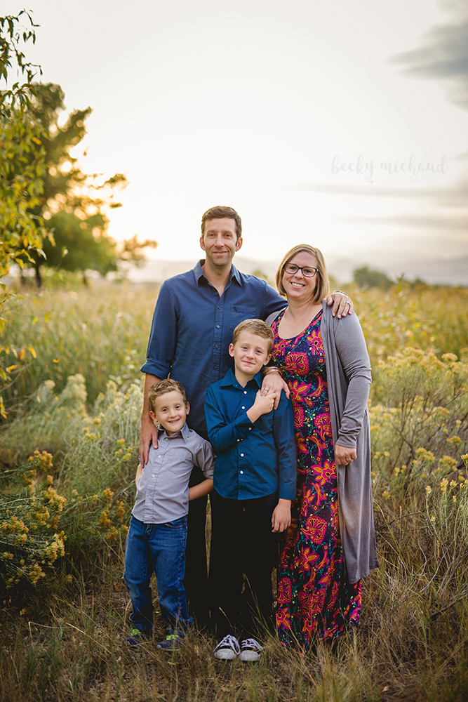 A family of four stands in a field together in Loveland, Colorado on a beautiful fall day