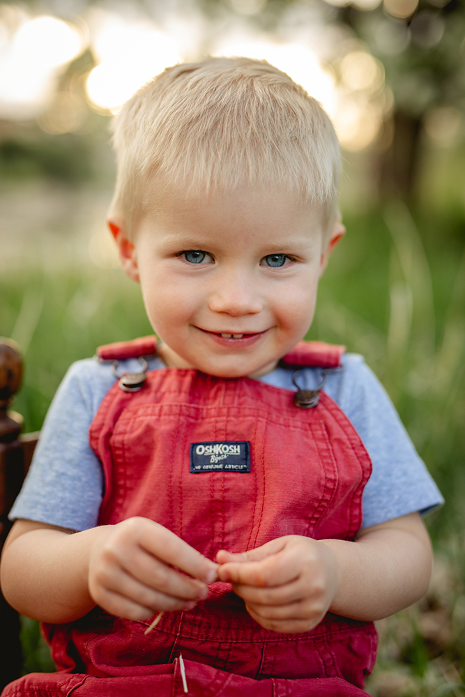 Portrait of a toddler in red overalls taken by Becky Michaud, Loveland Photographer