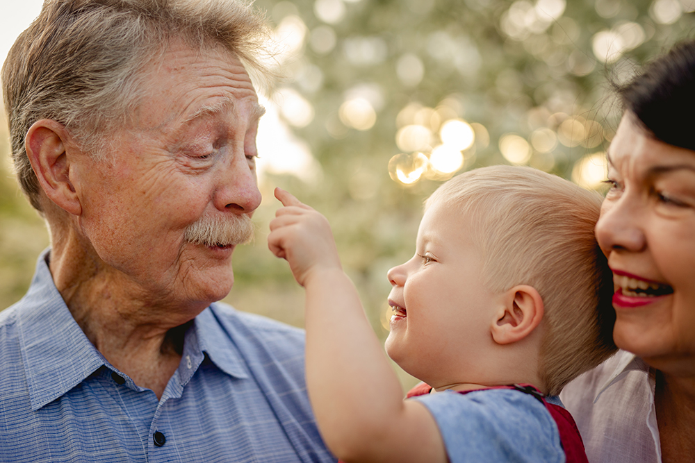 A toddler plays with his grandparents at their Loveland, Colorado extended family photo session