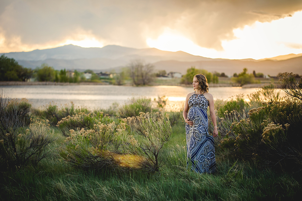 A pregnant mother looks out over the mountains as the sun sets behind her during her Loveland, Colorado maternity photo shoot