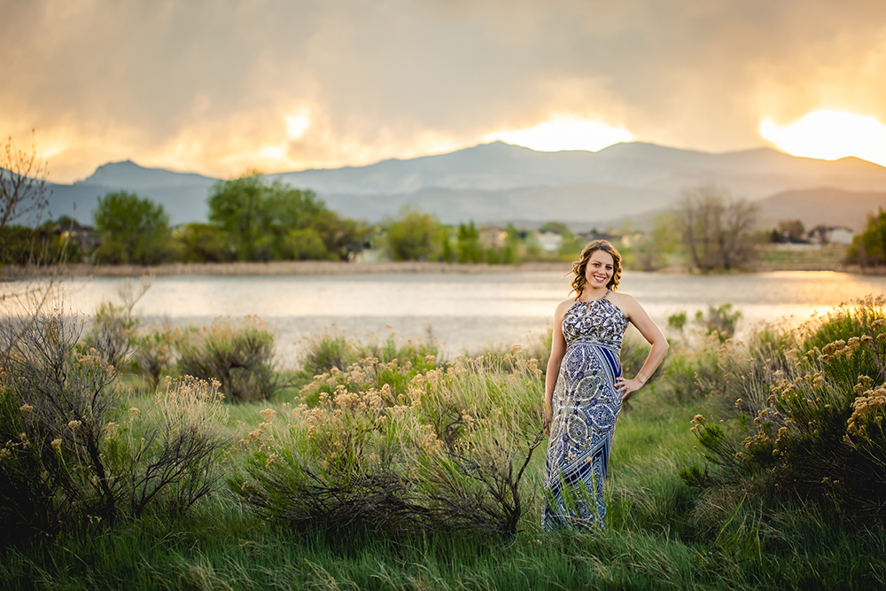 A Fort Collins, Colorado photographer specializing in newborns, maternity, and families took this photo of an expectant mother posing by a lake at sunset