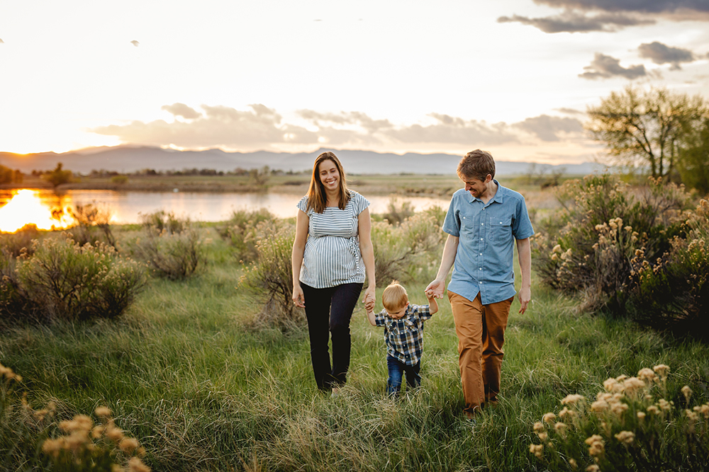 A family of three walks by the lake at sunset during their Loveland, Colorado maternity photo session