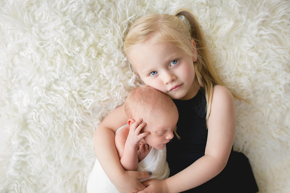 A big sister snuggles with her new baby brother in a photo taken by Becky Michaud, Fort Collins newborn photographer