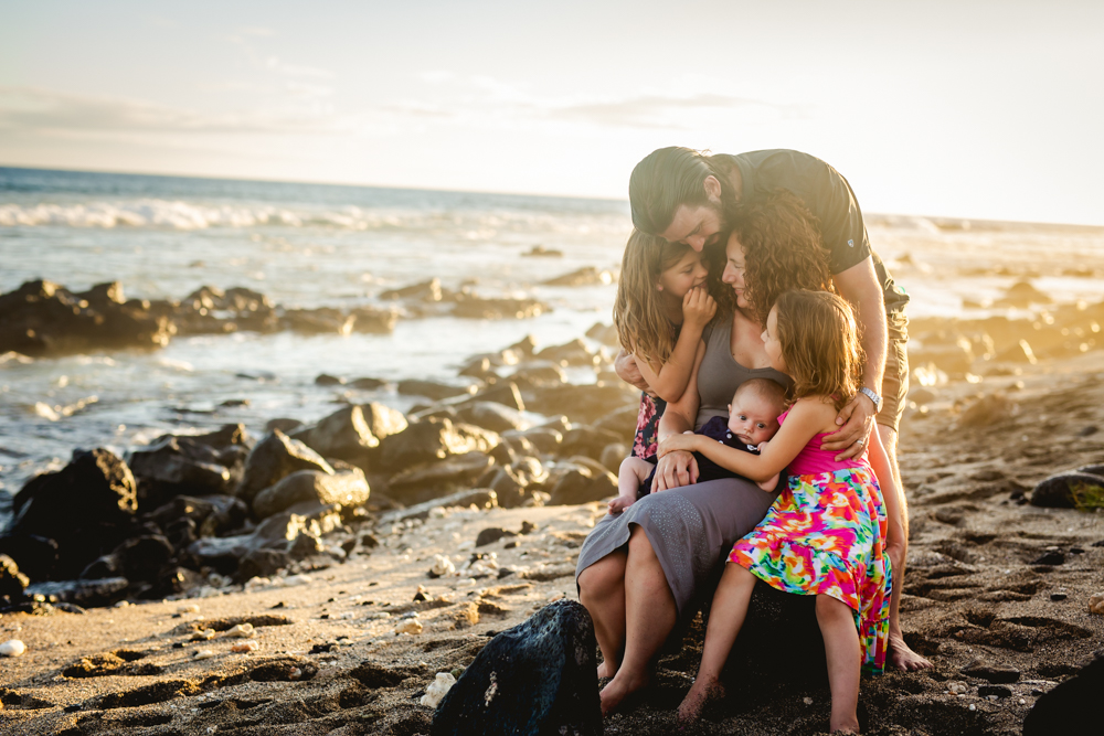 A family of five snuggles together on the beach on the big island of Hawaii during their family photography session