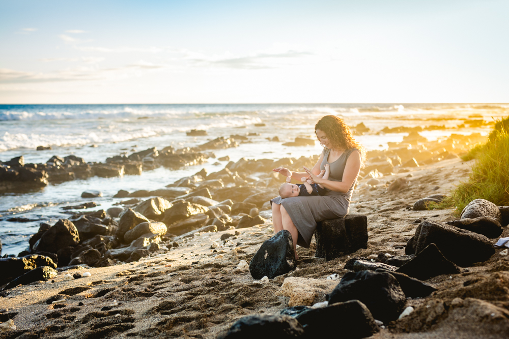 A mom plays with her baby son while the sun sets over the ocean in Hawaii