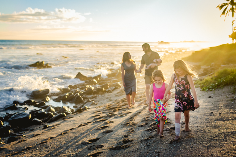 Two girls walk on the beach with their parents and baby brother behind them during their family photo session at Old Airport Beach