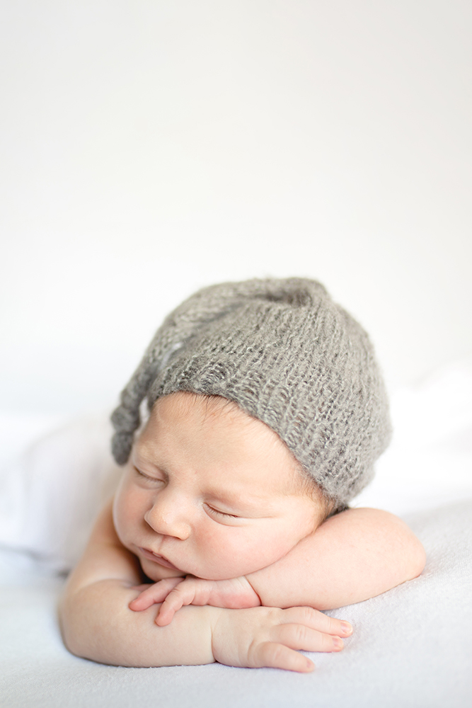 Simple newborn photo on a white backdrop taken in baby's Johnstown Colorado home