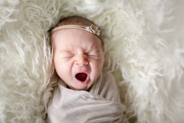 Photo of a yawning baby taken in Loveland, Colorado during her newborn photo session in her home