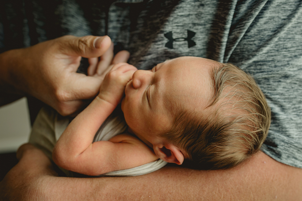 A baby holds on to his dad's hand in their Wellington, Colorado home