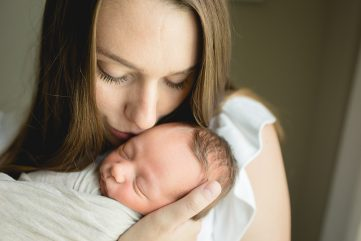 mom kisses her baby boy in a photo taken as part of their newborn photography session in their home in northern Colorado