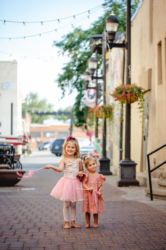 Two little girls pose in an alley in Old Town Fort Collins during their photography session