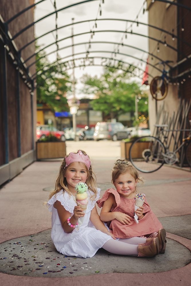 Two sisters eat ice cream together during their Old Town Fort Collins photography session