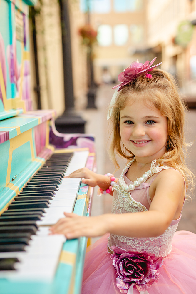 A little girl plays a piano in Fort Collins' Old Town area as a part of her four year old photos