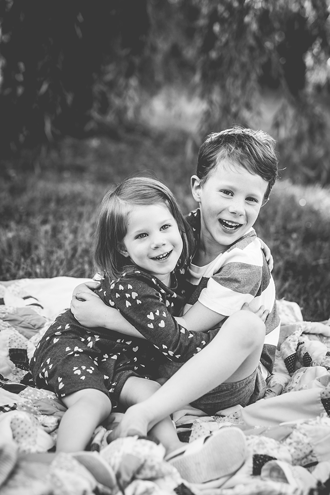 Brother and sister hug and laugh together during their family photo session