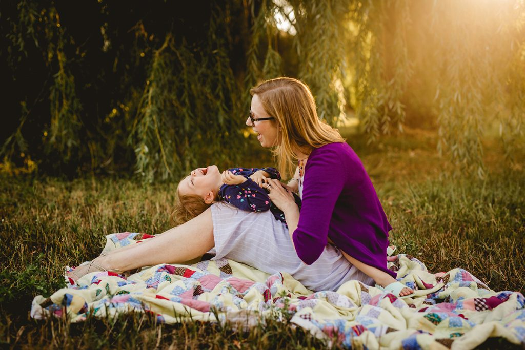 Mom tickles her daughter under a willow tree as they pose for their family photos in Fort Collins, Colorado