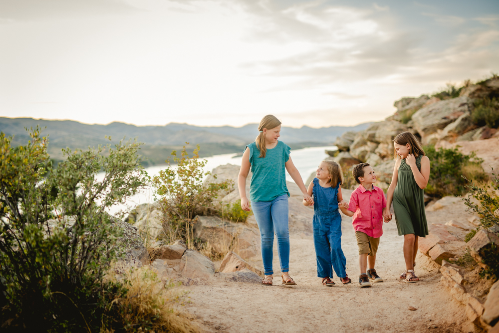 Four siblings walk together at Horsetooth Reservoir during their summertime family photo session