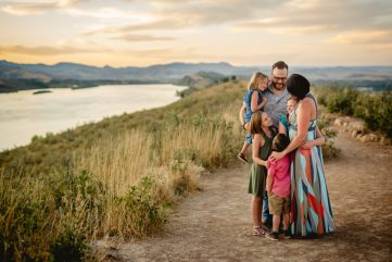 A family of six stands on a hill at Horsetooth Reservoir as the sunsets over the foothills