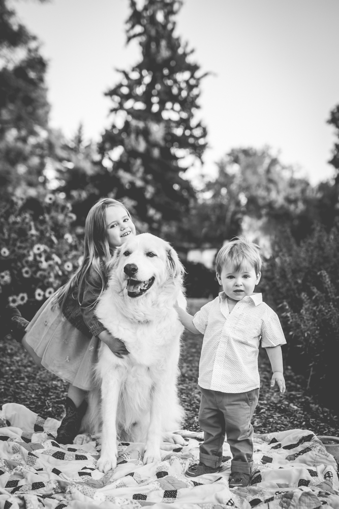 Black and white photo of two kids with their family dog, taken by Becky Michaud, Fort Collins photographer