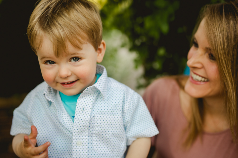 A little boy smiles as he poses with his mom during their Fort Collins family photo shoot