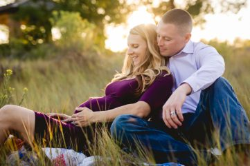 A couple cuddles together as they take their maternity photos at a Loveland, Colorado park