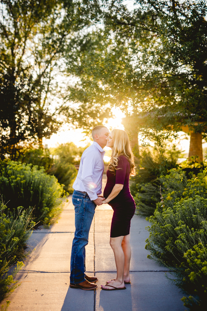 A couple kisses on a pathway during their maternity photo session in Loveland, Colorado