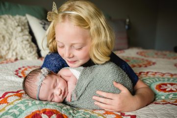 A girl smiles at her newborn baby sister during their in home newborn photography session in Fort Collins