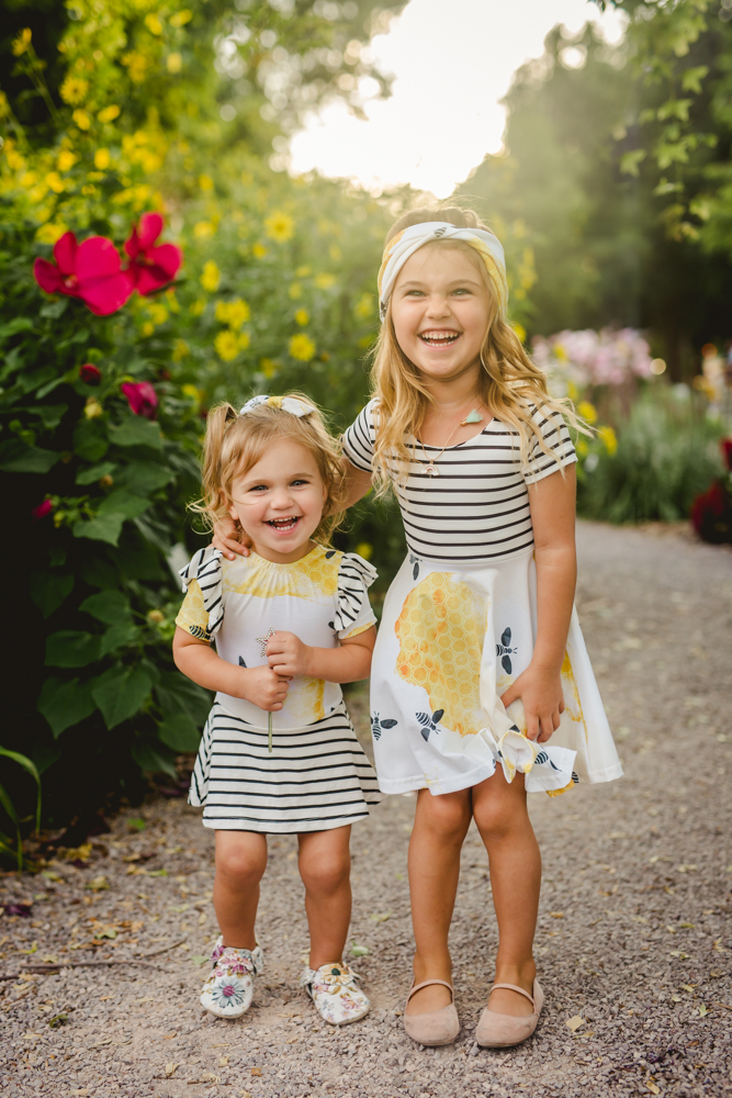 Sisters laugh together in a flower garden in Fort Collins, Colorado