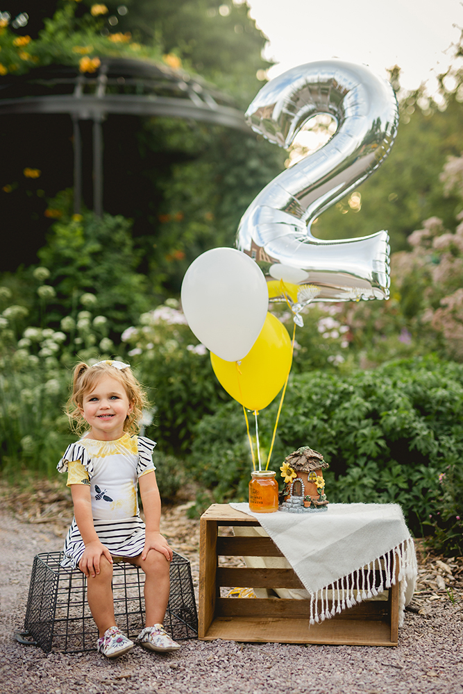 A two year old poses with her bee themed birthday decor as part of her photography session at a Colorado flower garden