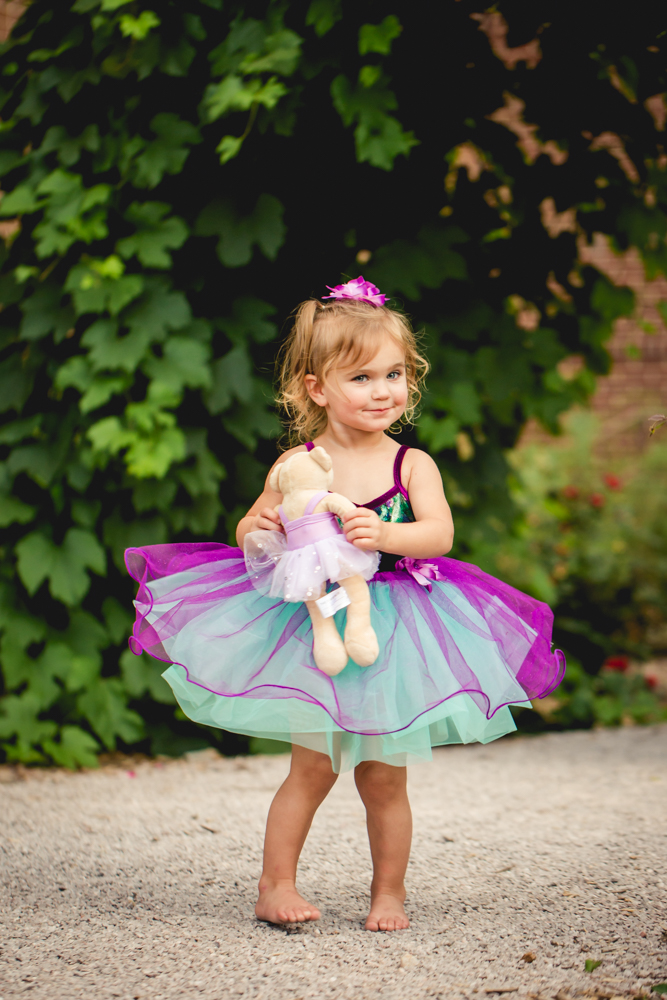 A little girl dances with her teddy bear during her Fort Collins photo session at the CSU Trial Gardens