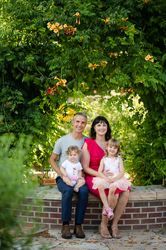 A family of four sits on a bench under green vines for their family photo session at the CSU Trial Gardens