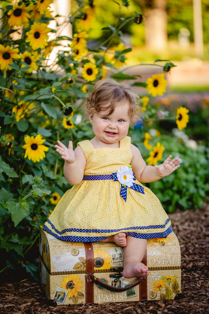 A baby girl sits by some sunflowers in a portrait taken by Becky Michaud, Fort Collins baby photographer