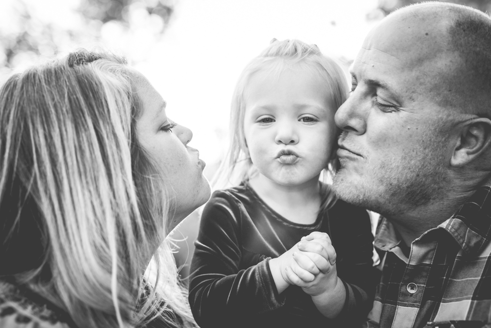 A girl puckers up as her parents kiss her on the cheeks during their family portraits