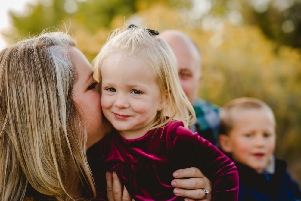A little girl smirks as her mom whispers in her ear during their family photo session at a Fort Collins natural area