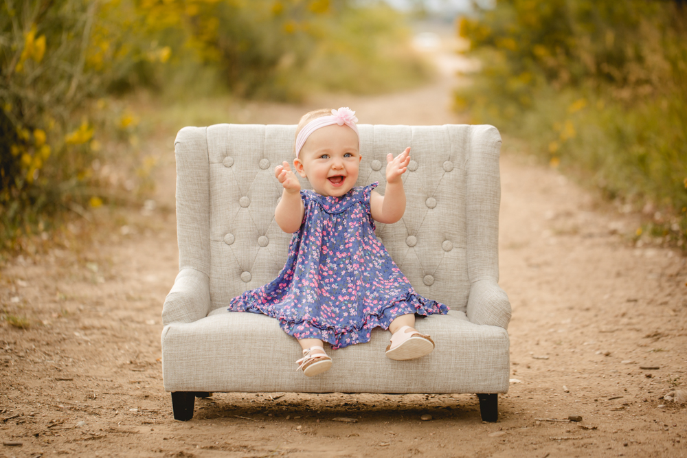 A one year old girl sits on a couch and claps her hands at Arapahoe Bend Natural Area in Northern Colorado