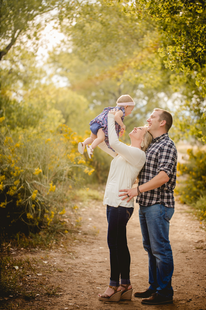 A mom and dad play with their daughter during their family photography session in Fort Collins