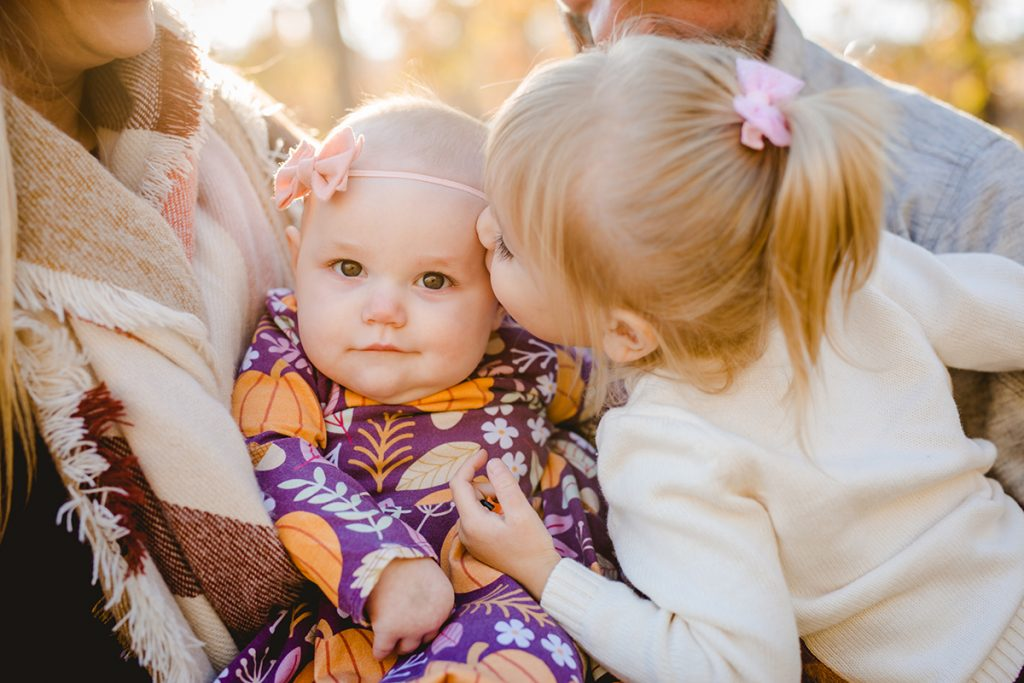 A little girl kisses her baby sister in a photo taken by Becky Michaud, Northern Colorado photographer